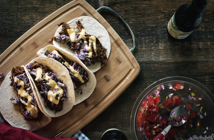 BBQ Brisket Tacos with Dubliner Cheese Sauce on a cutting board