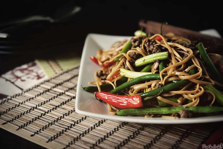 Szechuan noodles with vegetables and beef on a white plate