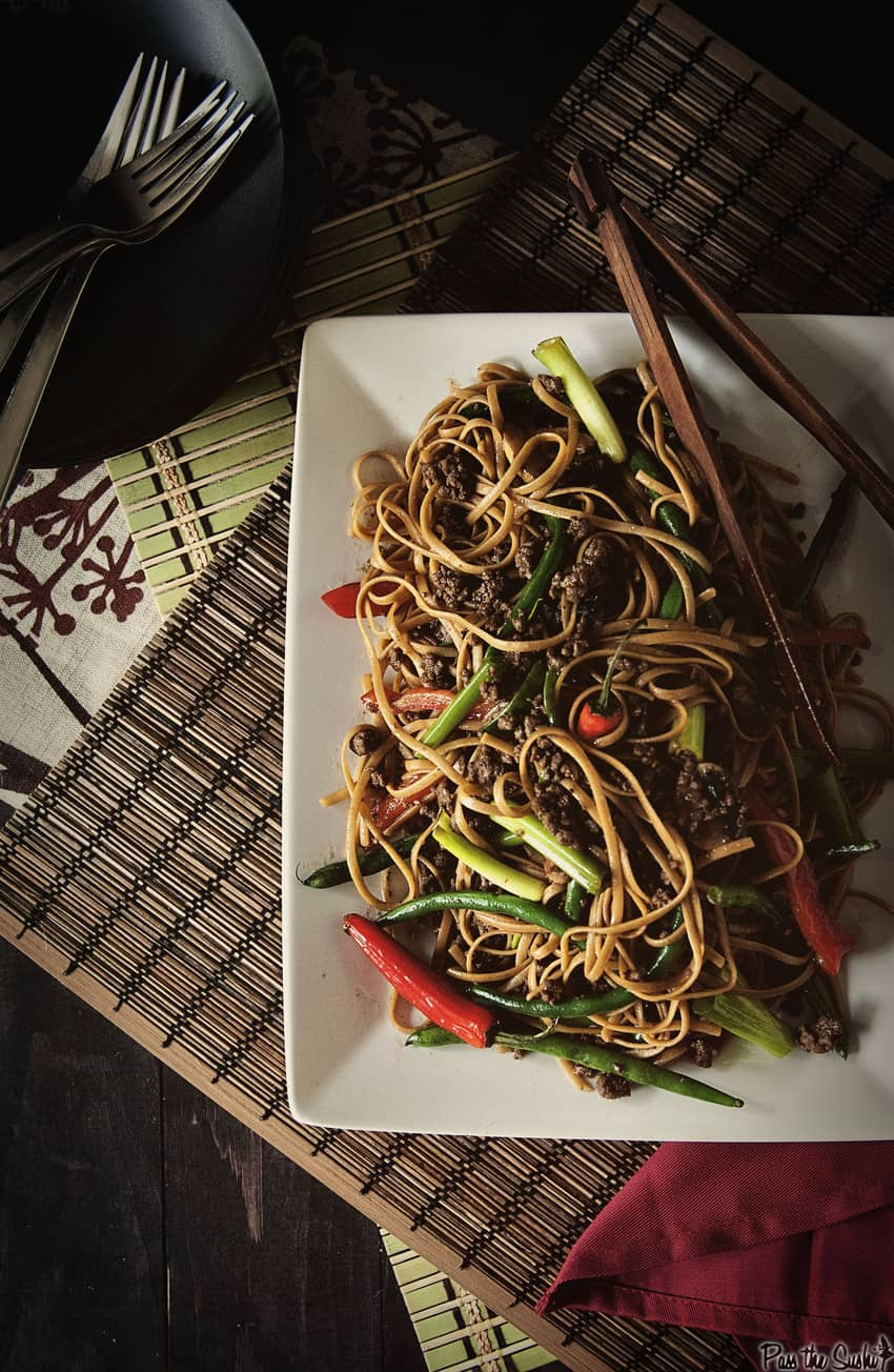 Szechuan beef noodles with vegetables on a white plate