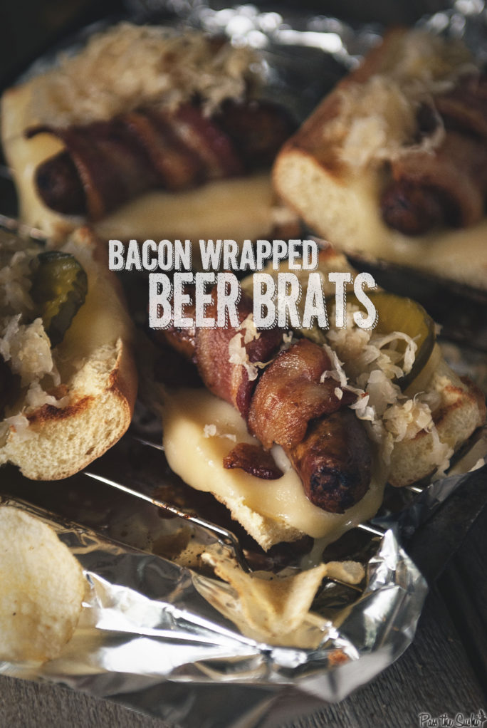 Bacon Wrapped Beer Brats on toasted bread with pickles and onion on aluminium foil and a side of chips