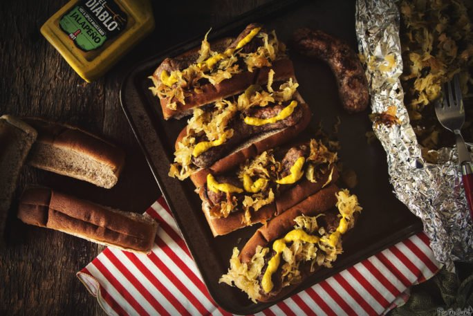 Four plump brats just loaded up with Spicy Mustard and Sauerkraut. Grab a plate, it's go time!