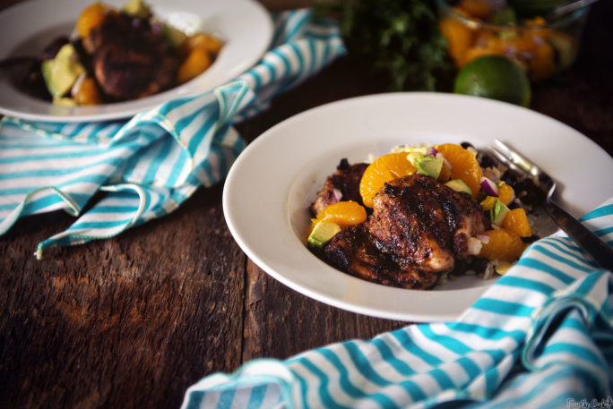 Two plates of Jerk Chicken with Avocado-Orange Salsa, set out picnic style. Grab a fork!