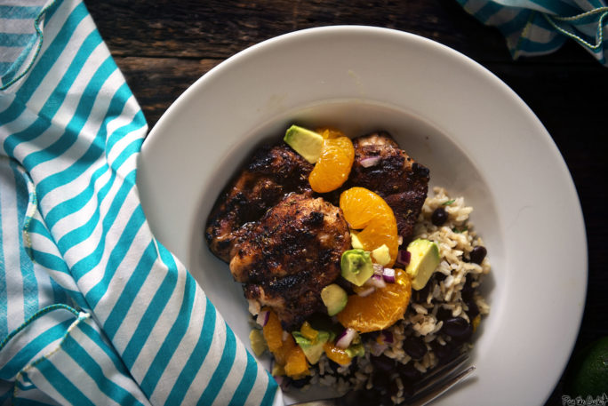 Jerk Chicken over a bed of rice and beans topped with a magnificent pie of avocado-orange salsa.
