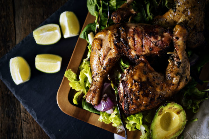 Smoked Leg Quarters over a bed of greens with Grilled Avocado, Scallion, and Red Onion piled around.