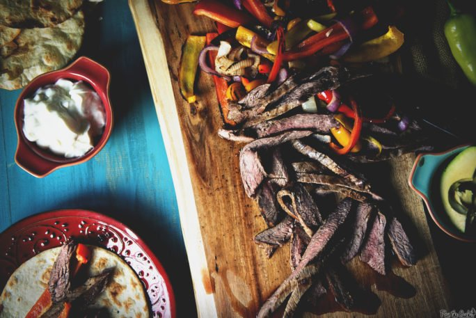 Just looking at these strips of tender beef is making me hungry! laid out with peppers, onions, avocado and sour cream, they are ready to fill your fajita!