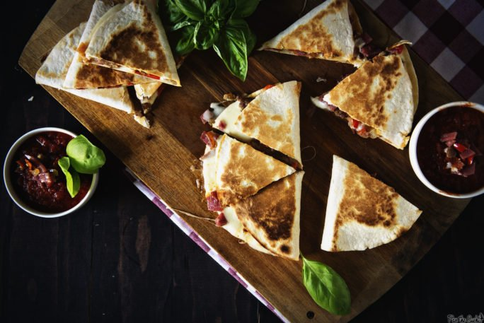 This quesadilla is all cut up and ready to go. Meat and cheese spilling out everywhere. Grab a slice, and a napkin!