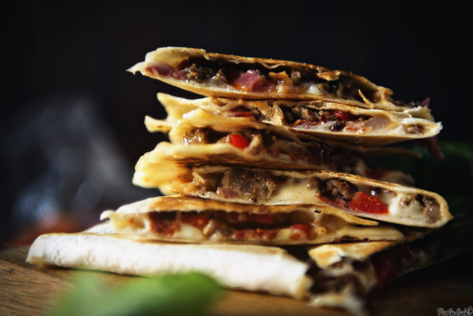 A stack of meat filled quesadilla slices. So much meat!