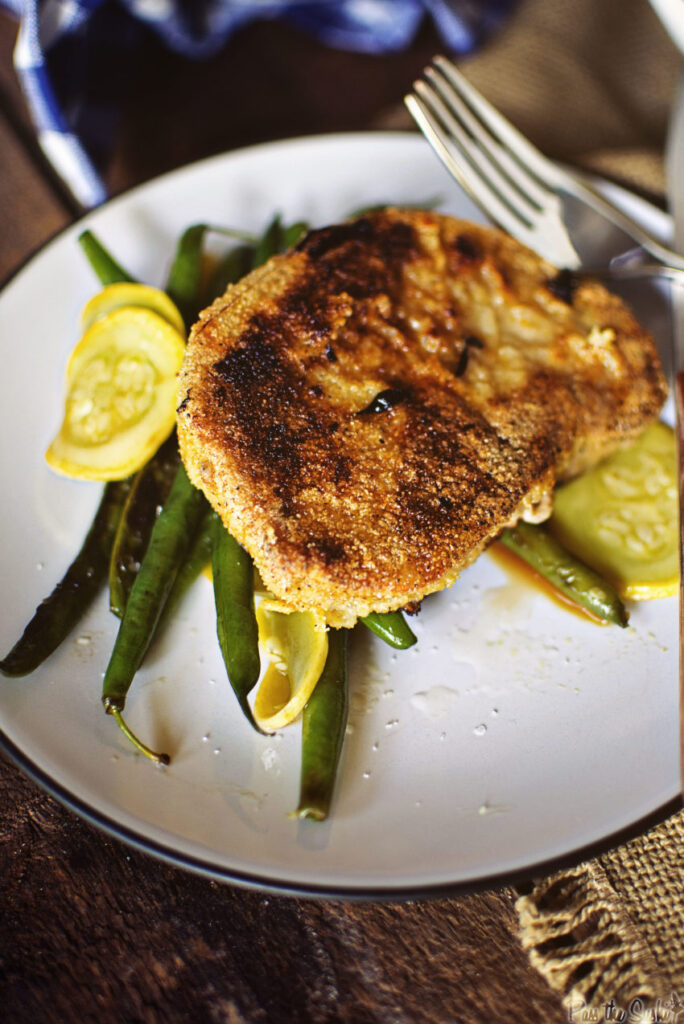 A Cornmeal crusted Pork Chop over green beans. Dig in to your new favorite meal!