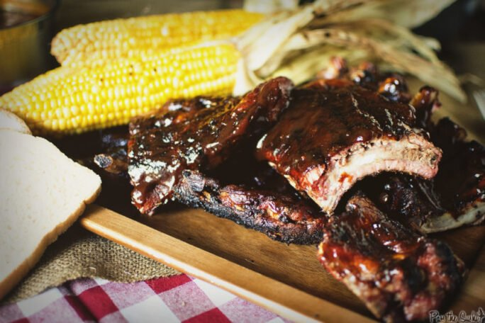 These Grilled Barbecue Baby Back Ribs look so good! Fresh corn on the side, and BBQ sauce dripping everywhere!