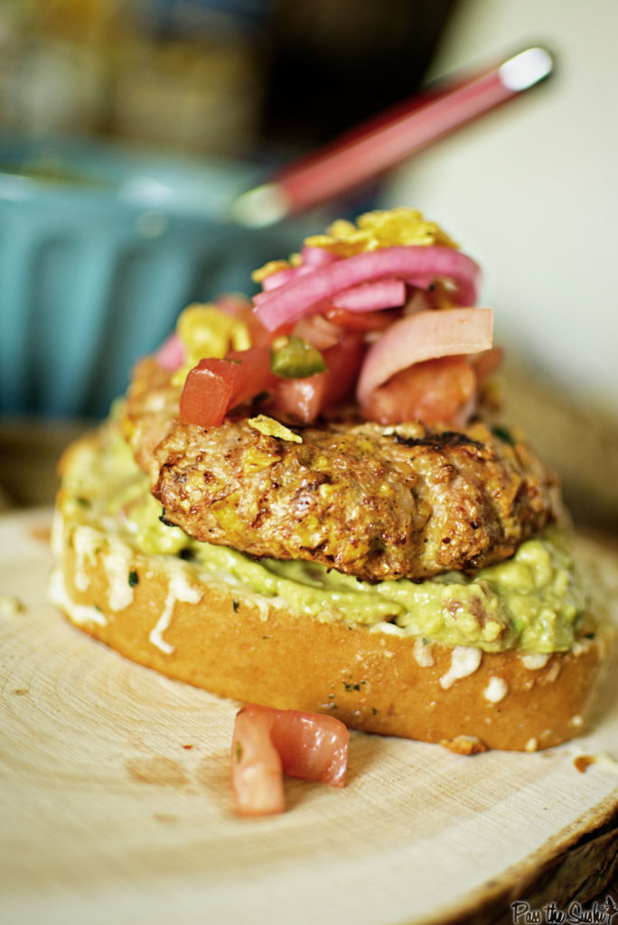 A plump chicken patty topped with tomato, red onion, and nestled on a bed of avocado smear. Yeah, this is a good one!