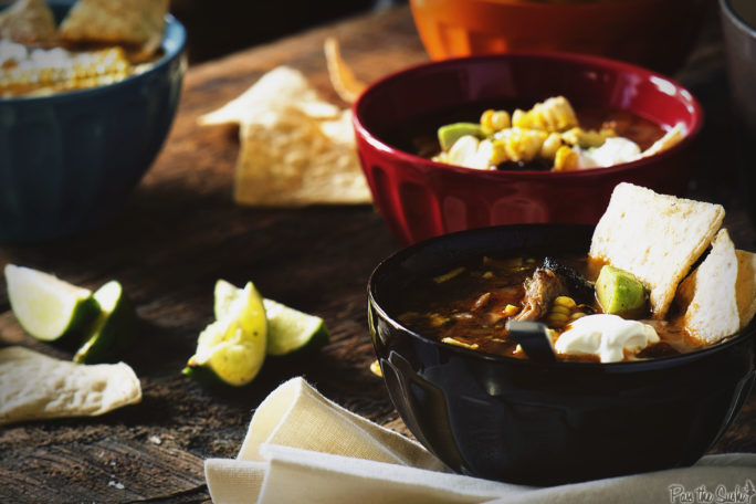 Three bowls filled with glorious Chicken Tortilla Soup, with loads of limes, veggies, tortilla chips and sour cream to go around!