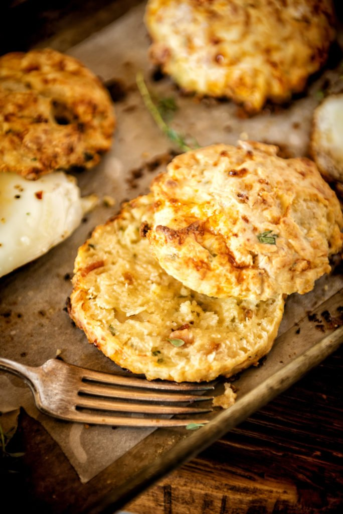A cheesy buttery biscuit sliced in half. perfect crumbs and flecks of herbs.