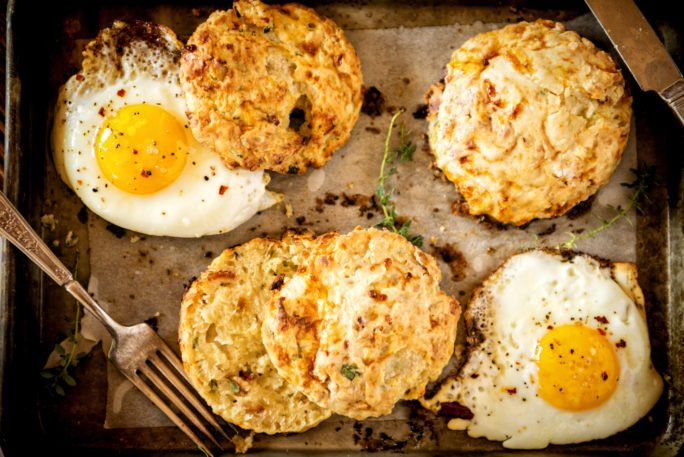 Herb and Bacon Cottage Cheese Biscuits with eggs on a sheet-pan. grab a fork.