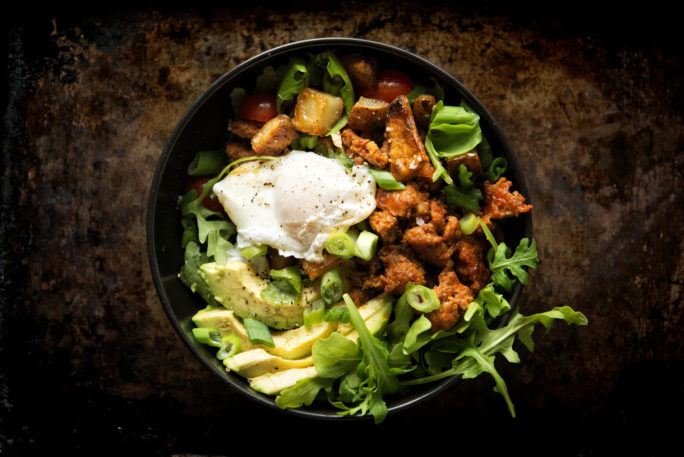 A poached egg nested on top of a bed of chorizo, avocado, home fries and arugula. You've got to try this!