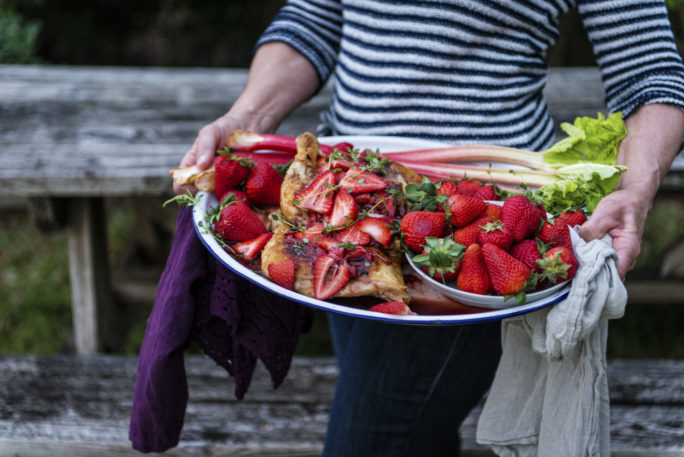 Heaping tray of Roasted Chicken and Strawberries in the arms of Mamma Ally.
