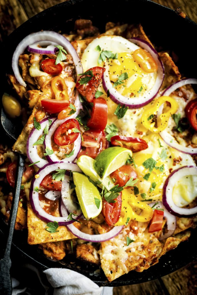 Smoked Chicken Chilaquiles breakfast recipe in a cast iron skillet topped with tomatoes limes and slices of red onion