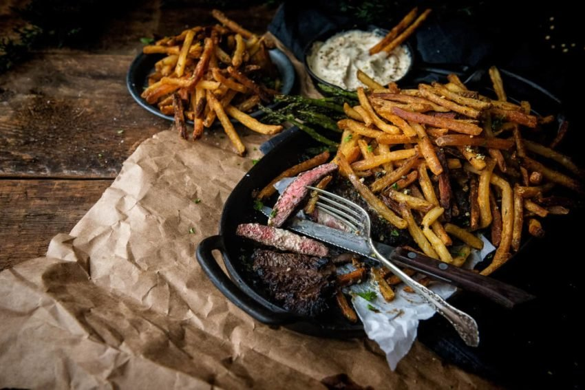 Steak Frites on a cast iron platter with rosemary duck fat fries. This is a meal you're gonna rave about!