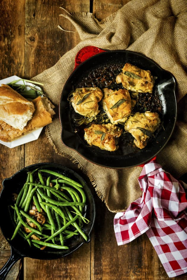 pan seared chicken thighs with crispy skin in red pan with herbs, green beans and bread on the side