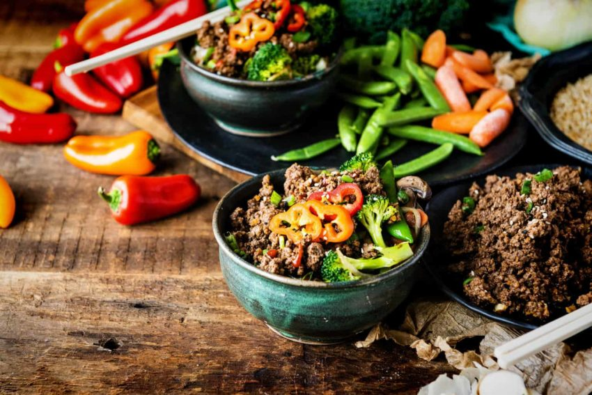 Beef and veggies piled together in a bowl, tons more of everything laid out. Look at those peppers! This is a fresh, healthy meal that will seriously fuel you up!