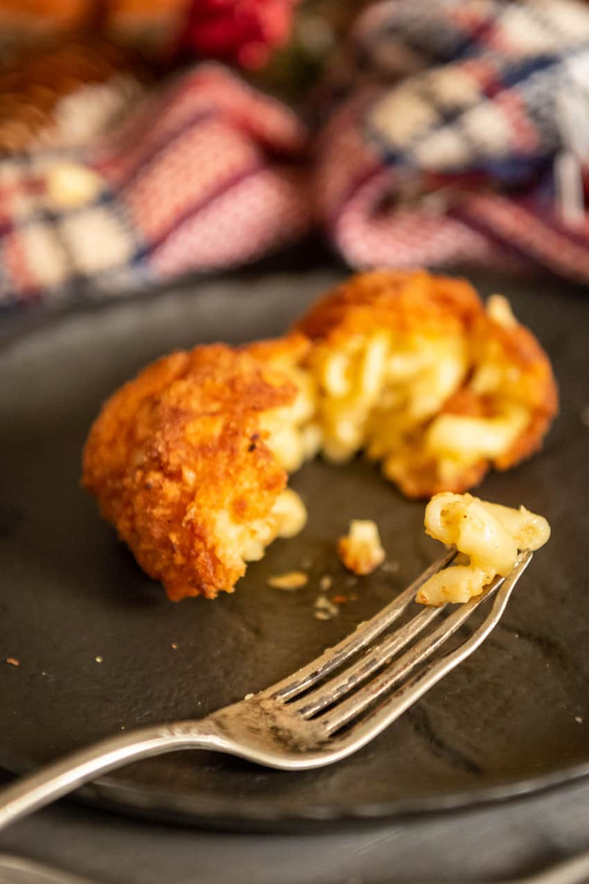 Deep fried macaroni and cheese ball broken apart with a bite of elbow pasta on the end of a fork