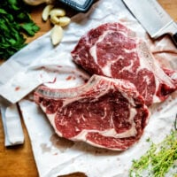 Two raw bone in ribeye steaks with salt, garlic and herbs around them