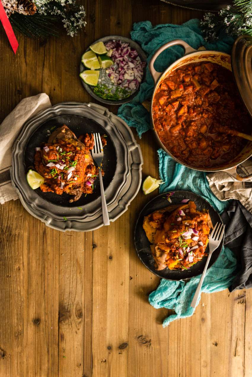A heavy cast iron pot of chili. A plate of toppings. And two sweet potatoes on plates that have be absolutely buried in this amazing meaty mess. So good!