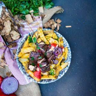 Grilled beef heart kabob recipe over thick cut potatoes with a simple sauce and grilled onions and peppers on a simple background with wood chips and herbs