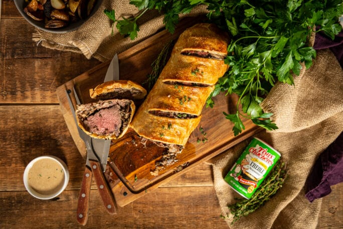 Sliced Beef Wellington arranged on a cutting board with brandy cream sauce and Tony Chachere's spices