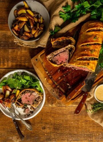 classic beef wellington sliced on a cutting board and a serving on a plate with potatoes and greens.