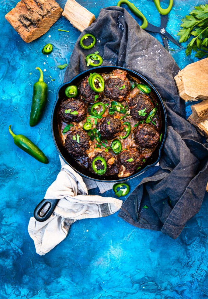 skillet filled with smoked jalapeno popper meatballs and sliced fresh jalapeno