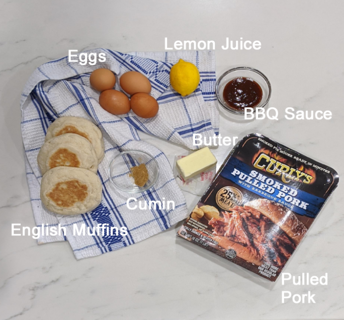 overhead ingredient shot for bbq eggs benedict; muffins, eggs, lemon, butter, cumin, bbq sauce, and pulled pork in packaging