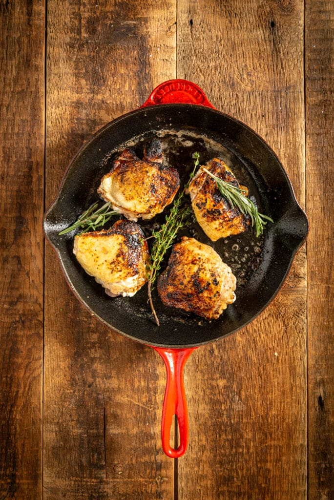chicken thighs seared and flipped in a skillet before cooking in the oven with herbs
