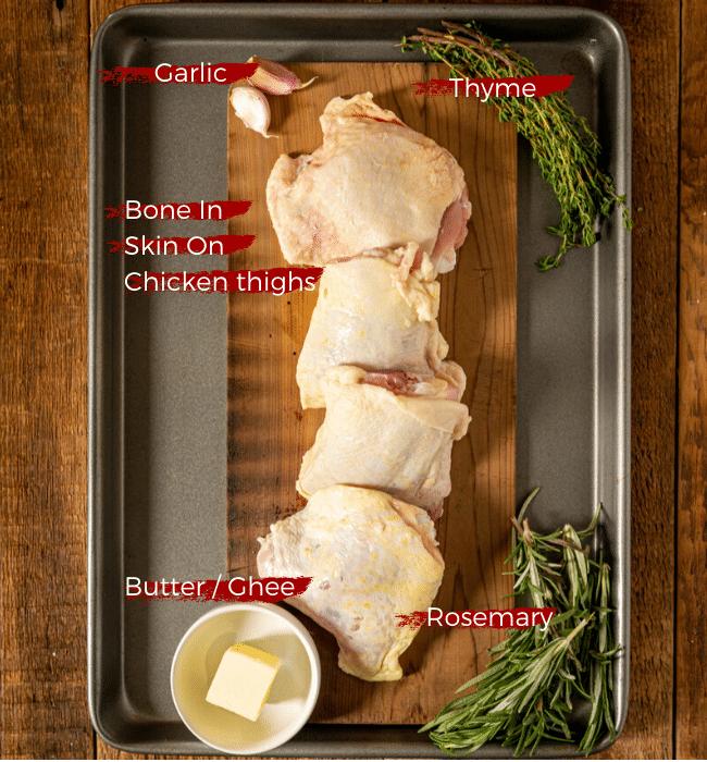 Ingredients for pan seared chicken thighs. Raw chicken, herbs, garlic, butter