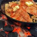 2 tilapia fillets topped with butter in cast iron skillet over hot charcoal