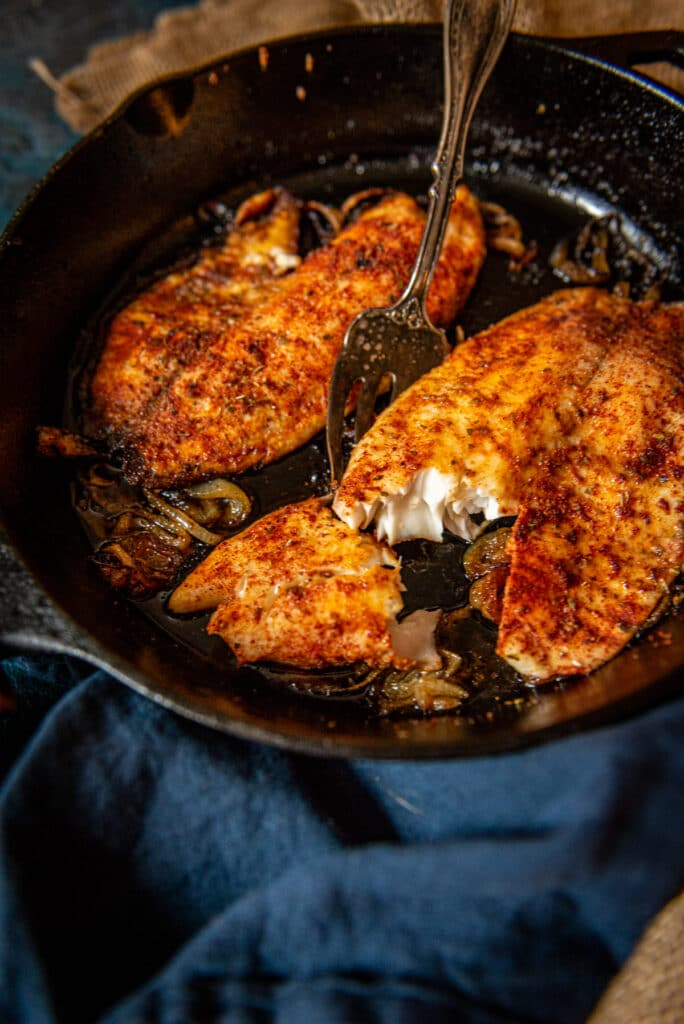 2 paprika coated cooked tilapia filets in a cast iron skillet