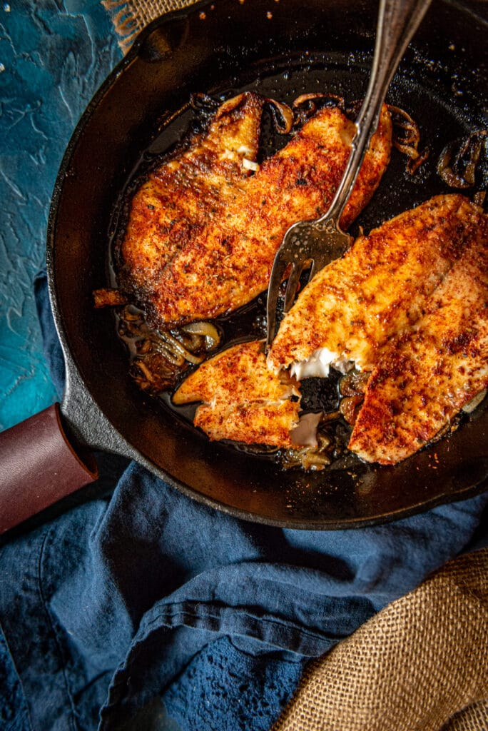 2 tilapia fillets in a cast iron skillet, one showing flakey tender white meat