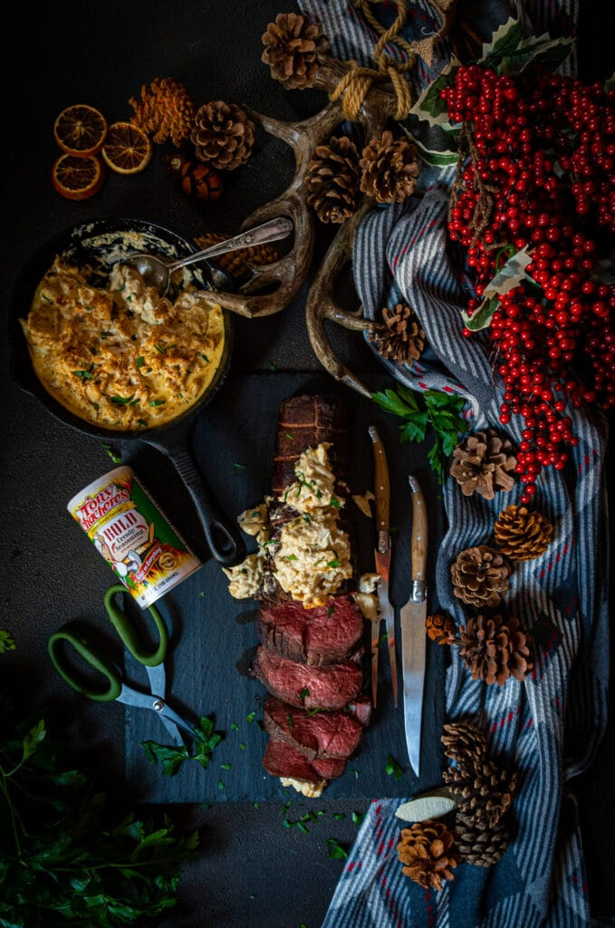 above image of a smoked tenderloin sliced and topped with crab imperial on a table decorated for the holidays
