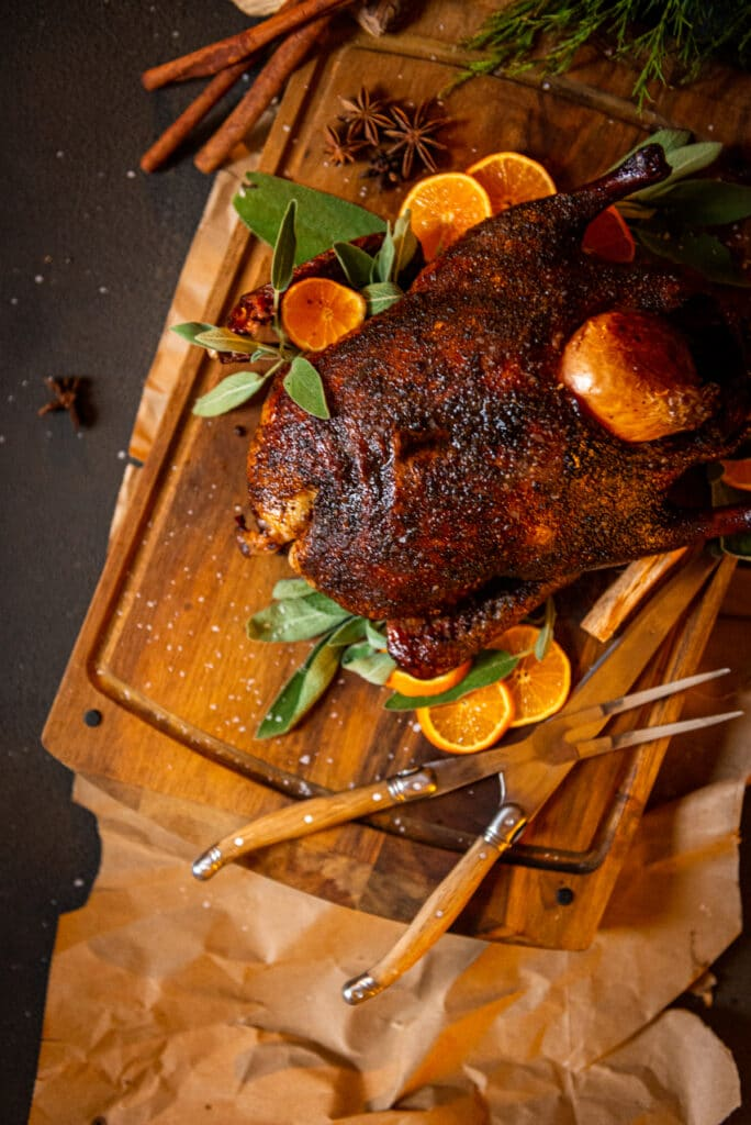 Smoked duck on a wood cutting board with sage and oranges