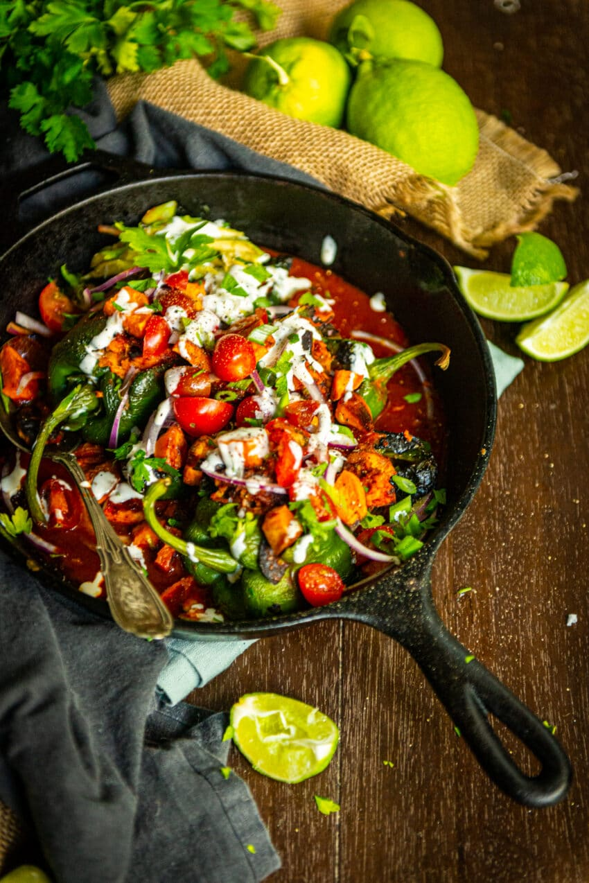 cast iron skillet filled with chicken tinga stuffed poblanos and various toppings