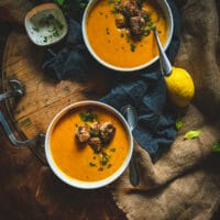 Big bowls of carrot soup with turkey meatballs and parlsey garnish