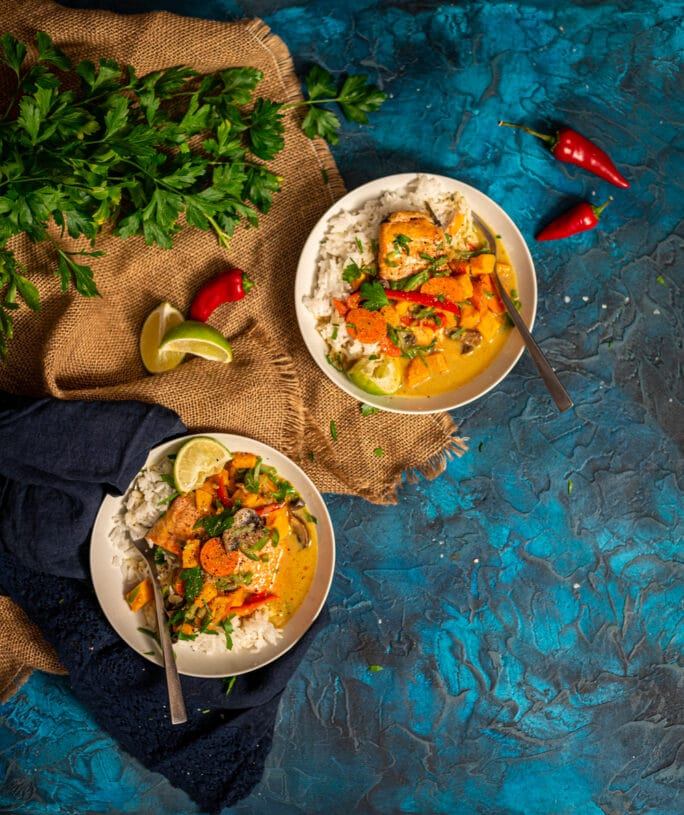 above shot of two bowls of comforting salmon curry with veggies over rice