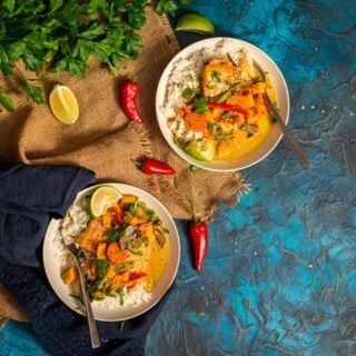2 bowls of salmon curry over rice with peppers and herbs laying about