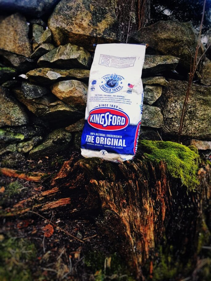 bag of kingsfod charcoal on a tree stump