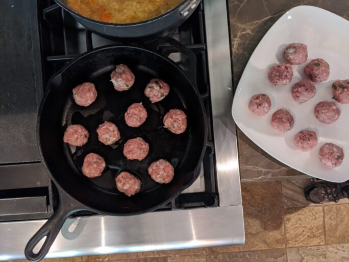 turkey meatballs with ginger being pan seared in cast iron