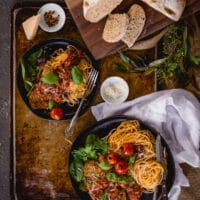 Beef parmesan with pasta on platters with greens and rustic bread