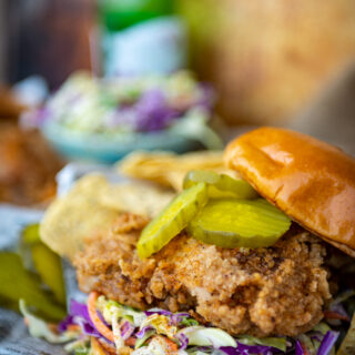 Close up of a fried chicken sandwich on a bun with creamy slaw and pickles on top with drink and more chicken in the background