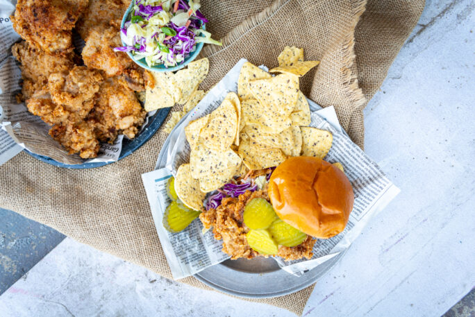 Above shot of fried chicken sandwich with chips and a platter of extra fried chicken and slaw
