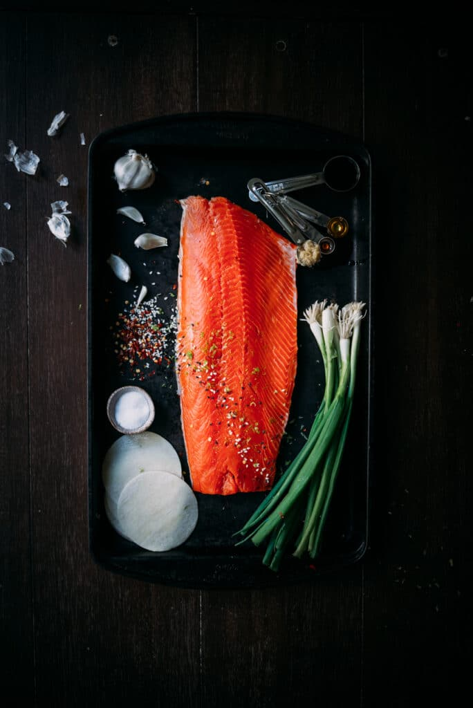 Fresh sockeye filet on platter with scallions, dumpling wrappers and ingredients