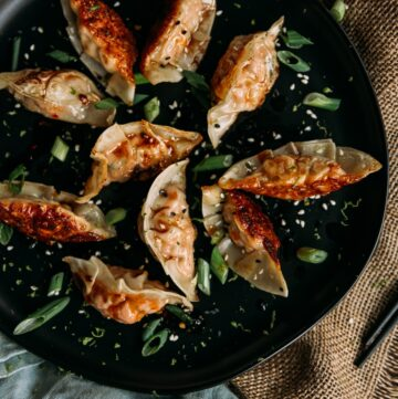 Salmon Potstickers on a black plate with sliced scallions and sesame seeds garnish
