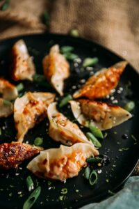 Homemade salmon potstickers on a black platter with crispy bottoms and scallions and sauce